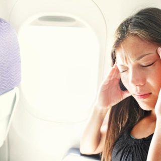 Kobieta trzymająca dłonie przy skroniach z bólu podczas lotu samolotem