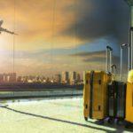 Dwie walizki w poczekalni na lotnisku na tle startującego samolotu