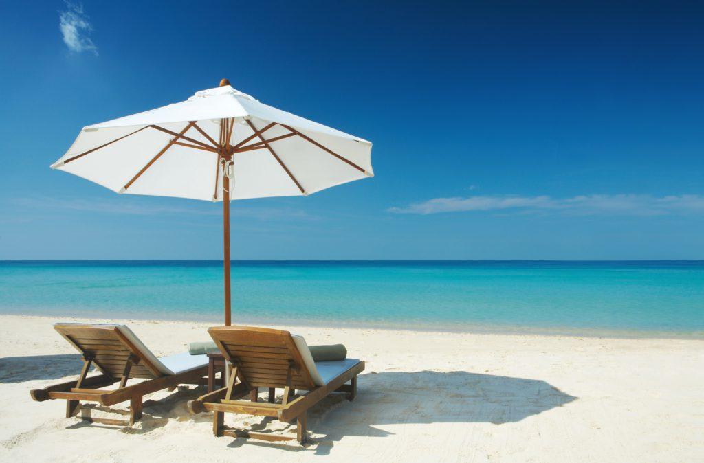 Parasol i dwa leżaki na plaży na tle błękitnego morza.