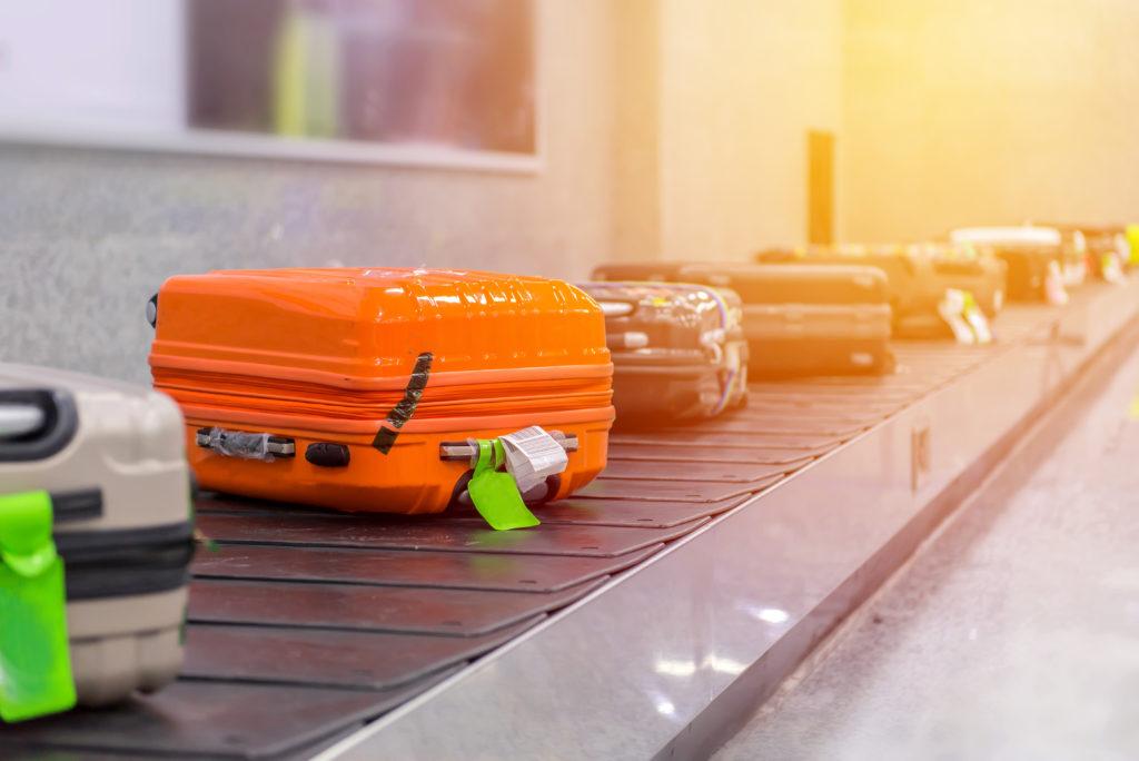 Walizki na taśmie w strefie odbioru bagażu na lotnisku.