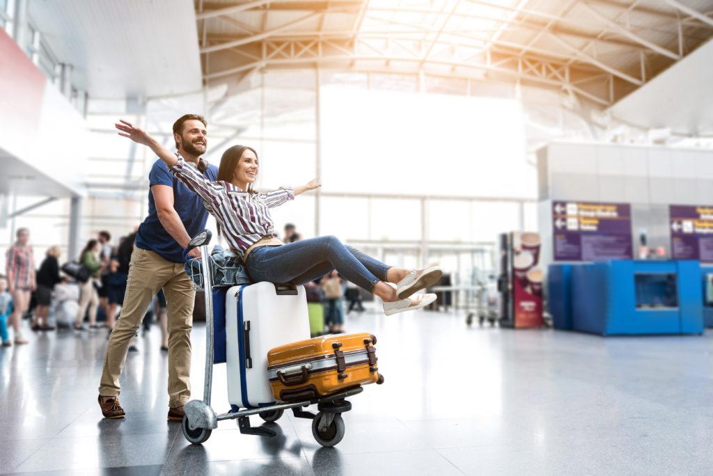 Wesoła para odbierająca bagaże na lotnisku.